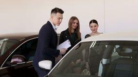 Δύο πολυτελή νέα κορίτσια σε μια συζήτηση εμποριών αυτοκινήτων σε έναν πωλητή αυτοκινήτων Πώληση αυτοκινήτων φιλμ μικρού μήκους