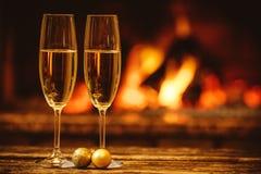 Δύο ποτήρια της λαμπιρίζοντας σαμπάνιας μπροστά από τη θερμή εστία Γ Στοκ Εικόνες
