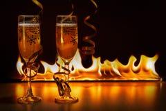 Δύο ποτήρια της λαμπιρίζοντας σαμπάνιας με τις χρυσές κορδέλλες στο κλίμα bokeh των φωτεινών φλογών που δημιουργεί έναν άνετο στοκ εικόνες