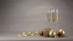 Δύο ποτήρια της σαμπάνιας είναι μεταξύ των παιχνιδιών Χριστουγέννων σε ένα γκρίζο υπόβαθρο απόθεμα βίντεο