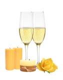 Δύο ποτήρια της σαμπάνιας, κεριά και κίτρινος αυξήθηκαν απομονωμένος Στοκ Φωτογραφίες