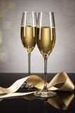 Δύο ποτήρια της σαμπάνιας με μια χρυσή κορδέλλα Στοκ Εικόνες