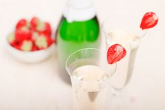 Δύο ποτήρια της σαμπάνιας με τις τεμαχισμένες φράουλες, ενάντια σε ένα BOT Στοκ Φωτογραφίες
