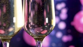 Δύο ποτήρια της σαμπάνιας με τις φυσαλίδες στο σκούρο μπλε να αναβοσβήσει υπόβαθρο απόθεμα βίντεο