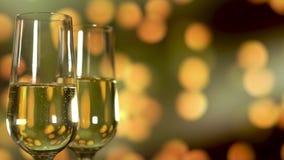 Δύο ποτήρια της σαμπάνιας με τις φυσαλίδες στο χρυσό να αναβοσβήσει υπόβαθρο απόθεμα βίντεο