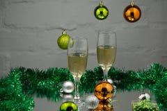 δύο ποτήρια της σαμπάνιας που στέκονται στον πίνακα στο υπόβαθρο ενός θολωμένου δωματίου με ένα διακοσμημένα χριστουγεννιάτικο δέ Στοκ Εικόνες