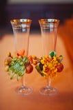Δύο ποτήρια της σαμπάνιας στο υπόβαθρο της γαμήλιας ανθοδέσμης των ρόδινων τριαντάφυλλων Μαλακή εστίαση, εκλεκτική εστίαση Στοκ Εικόνες