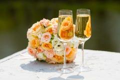 Δύο ποτήρια της σαμπάνιας στο υπόβαθρο της γαμήλιας ανθοδέσμης των τριαντάφυλλων Στοκ εικόνες με δικαίωμα ελεύθερης χρήσης