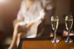 Δύο ποτήρια της σαμπάνιας στο υπόβαθρο το θηλυκό σκιαγραφούν Στοκ Εικόνες