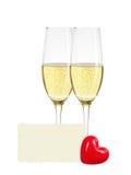 Δύο ποτήρια της σαμπάνιας, της ευχετήριας κάρτας και της κόκκινης καρδιάς που απομονώνονται Στοκ Φωτογραφία