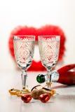 Δύο ποτήρια της σαμπάνιας, του φελλού, των γλυκών και του μπουκαλιού σαμπάνιας Στοκ Εικόνες