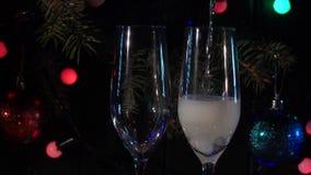 Δύο ποτήρια της foamy σαμπάνιας με τις φυσαλίδες στα πλαίσια του τρεμουλιάσματος ανάβουν το α κίνηση αργή κλείστε επάνω απόθεμα βίντεο
