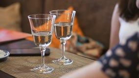 Δύο ποτήρια του άσπρου λαμπιρίζοντας κρασιού είναι στον πίνακα στο εστιατόριο Δύο γυναίκες χαλαρώνουν και μιλούν στο εστιατόριο φιλμ μικρού μήκους