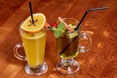 Δύο ποτήρια του θερμαμένου κρασιού με το πορτοκάλι, ραβδιά κανέλας Στοκ Εικόνες
