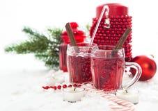 Δύο ποτήρια του θερμαμένων κρασιού και του κεριού με τις διακοσμήσεις Χριστουγέννων στοκ εικόνα