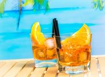 Δύο ποτήρια του κοκτέιλ aperol απεριτίφ spritz με τις πορτοκαλιούς φέτες και τους κύβους πάγου στην παραλία θαμπάδων και το υπόβα Στοκ Φωτογραφία