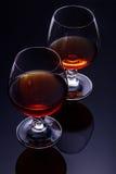 Δύο ποτήρια του κονιάκ σε ένα σκοτεινό υπόβαθρο με την αντανάκλαση Στοκ εικόνες με δικαίωμα ελεύθερης χρήσης