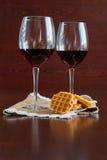 Δύο ποτήρια του κρασιού σε έναν ξύλινο πίνακα βάφλες στοκ εικόνα