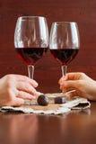 Δύο ποτήρια του κρασιού σε έναν ξύλινο πίνακα Καραμέλες Χέρια στοκ εικόνες με δικαίωμα ελεύθερης χρήσης