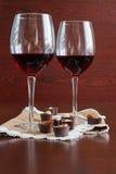 Δύο ποτήρια του κρασιού σε έναν ξύλινο πίνακα Καραμέλες στοκ εικόνα