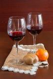 Δύο ποτήρια του κρασιού σε έναν ξύλινο πίνακα καρποί στοκ φωτογραφία