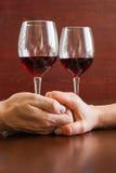 Δύο ποτήρια του κρασιού σε έναν ξύλινο πίνακα Χέρια στοκ φωτογραφίες με δικαίωμα ελεύθερης χρήσης
