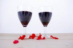 Δύο ποτήρια του κρασιού σε έναν πίνακα με τα πέταλα λουλουδιών Στοκ Εικόνες