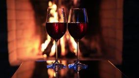 Δύο ποτήρια του κόκκινου κρασιού κοντά σε μια εστία απόθεμα βίντεο