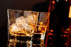Δύο ποτήρια του ουίσκυ μπροστά από το μπουκάλι ουίσκυ Στοκ Εικόνα