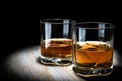 Δύο ποτήρια του ουίσκυ σε έναν εκλεκτής ποιότητας ξύλινο πίνακα σε ένα μαύρο υπόβαθρο στοκ εικόνες με δικαίωμα ελεύθερης χρήσης