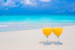 Δύο ποτήρια του χυμού από πορτοκάλι στην τροπική άσπρη παραλία Στοκ εικόνες με δικαίωμα ελεύθερης χρήσης