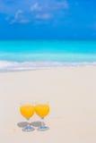 Δύο ποτήρια του χυμού από πορτοκάλι στην τροπική άσπρη παραλία Στοκ φωτογραφία με δικαίωμα ελεύθερης χρήσης