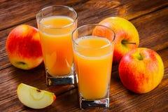 Δύο ποτήρια του χυμού και των μήλων της Apple σε ξύλινο Στοκ εικόνες με δικαίωμα ελεύθερης χρήσης