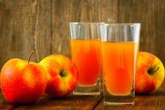 Δύο ποτήρια του χυμού και των μήλων της Apple σε ξύλινο Στοκ Φωτογραφία