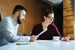 Δύο που συγκεντρώνονται businesspeople συζητώντας το πρόγραμμα στην αίθουσα συνεδριάσεων στοκ εικόνα