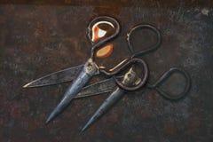 Δύο που το παλαιό μαύρο ψαλίδι μετάλλων είναι χειροποίητο, βρίσκονται το ένα πάνω από το άλλο σε ένα σκουριασμένο καφετί υπόβαθρο Στοκ Φωτογραφίες