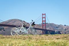 Δύο ποδήλατα που σταθμεύουν στη χλόη μπροστά από τη χρυσή γέφυρα πυλών Στοκ Φωτογραφία