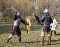Δύο πολεμιστές στην παλαιά ρωσική πάλη τεθωρακισμένων με τα ξίφη και τις ασπίδες Στοκ εικόνες με δικαίωμα ελεύθερης χρήσης
