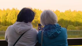 Δύο πρεσβύτεροι που παίρνουν selfie στο τηλέφωνο στεμένος στα κιγκλιδώματα κοντά στον ποταμό υπαίθρια απόθεμα βίντεο