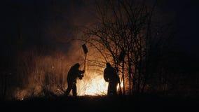 Δύο πυροσβέστες με τα πτερύγια πυρκαγιάς εξαφανίζουν μια πυρκαγιά στο δάσος τη νύχτα φιλμ μικρού μήκους