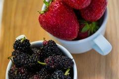 Δύο πλήρεις φράουλες και μουριές φλυτζανιών Στοκ εικόνες με δικαίωμα ελεύθερης χρήσης