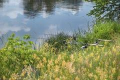 Δύο ράβδοι αλιείας που εξοπλίζονται με μια ηλεκτρονική συσκευή προειδοποίησης δαγκωμάτων στην όχθη ποταμού στοκ εικόνες