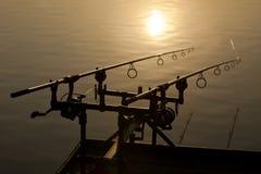 Δύο ράβδοι αλιείας στη σκιαγραφία Στοκ Φωτογραφία
