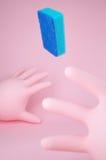 Δύο ρόδινα λαστιχένια γάντια και ένα πετώντας μπλε σφουγγάρι Στοκ φωτογραφία με δικαίωμα ελεύθερης χρήσης