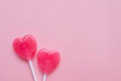 Δύο ρόδινη καραμέλα μορφής καρδιών ημέρας βαλεντίνων ` s lollipop στο κενό ρόδινο υπόβαθρο εγγράφου hipster ελάχιστη έννοια αγάπη στοκ εικόνες