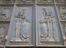 Δύο σκελετοί χάρασαν στο ξύλο στις πόρτες μιας παλαιάς εκκλησίας στην Πούλια στοκ φωτογραφίες με δικαίωμα ελεύθερης χρήσης