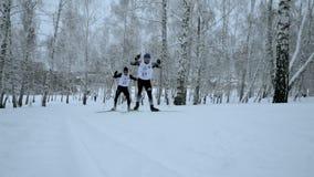 Δύο σκιέρ κλίνουν το σαλάχι κάνοντας σκι στα χιονώδη ξύλα φιλμ μικρού μήκους