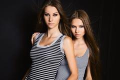 Δύο σοβαρές αδελφές φίλων στο μαύρο υπόβαθρο Στοκ φωτογραφία με δικαίωμα ελεύθερης χρήσης