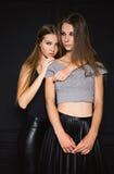 Δύο σοβαρές αδελφές φίλων στο μαύρο υπόβαθρο Στοκ Εικόνες