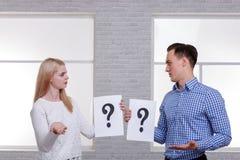 Δύο σοβαροί άνθρωποι, ένας τύπος και ένα κορίτσι, κρατούν ένα φύλλο με ένα ερωτηματικό και εξετάζουν ο ένας τον άλλον με την επιδ Στοκ Εικόνες